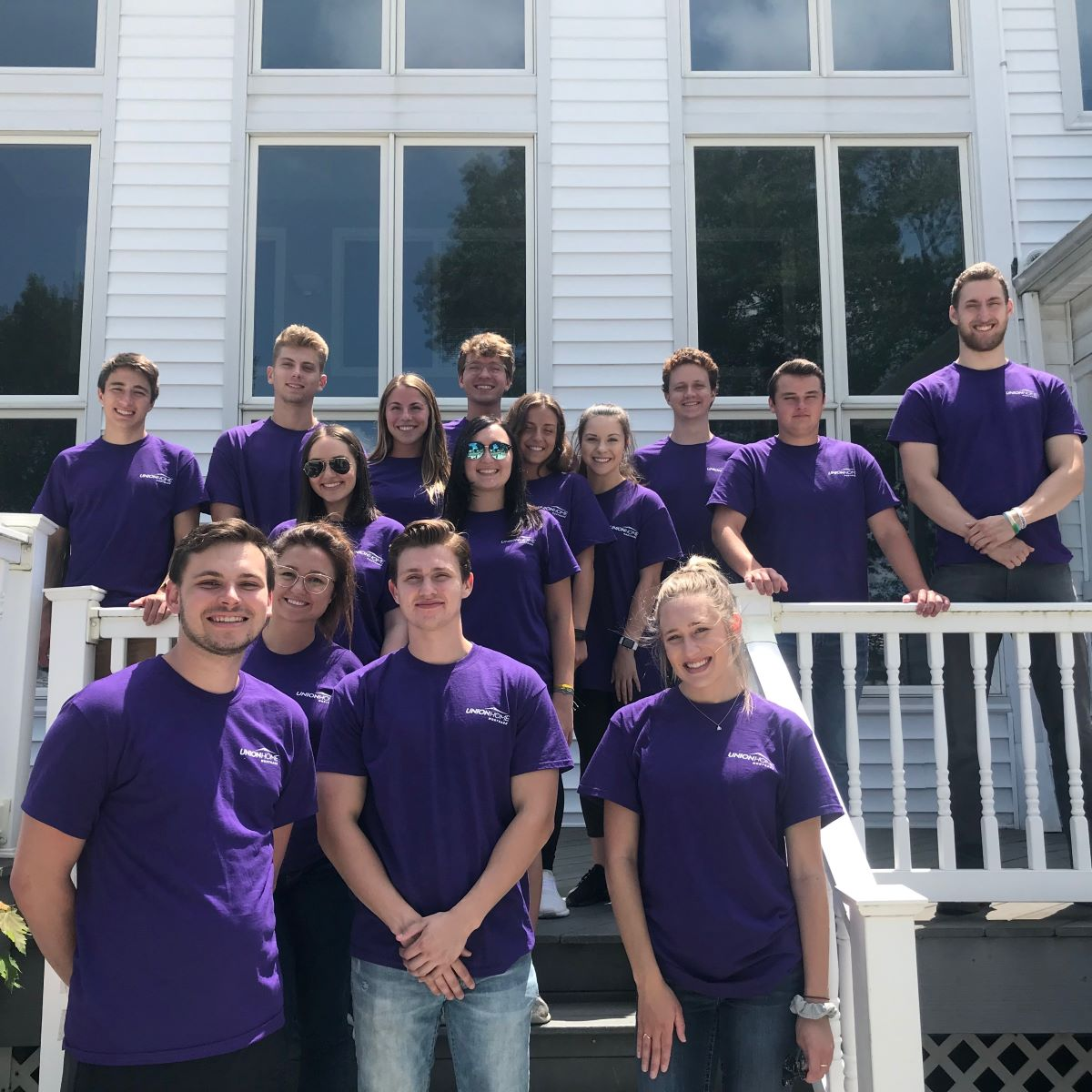 A group of interns in purple UHM volunteers shirts